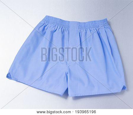 male underwear: blue boxershort over silver background