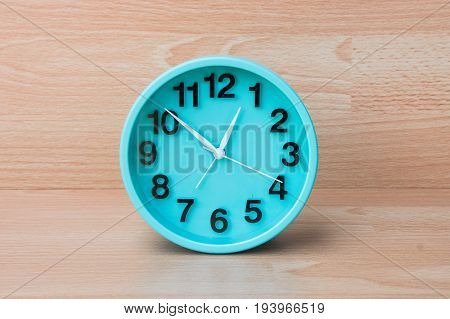 Green clock on wood background Clock to tell time Create a plan to manage the hustle of life or work.