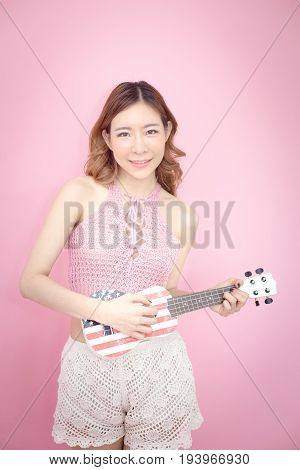 Beautiful Korea Woman Posing With Ukulele At Pink Background With Summer Concept, Isolated On Pink B