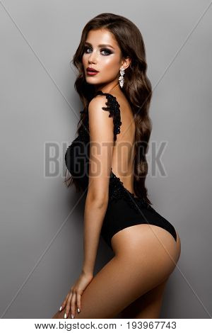 Stylish sexy girl in a black swimsuit isolated on a gray background, with curly hair and beautyful make up