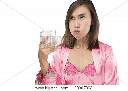 Woman rinsing and gargling while using mouthwash from a glass isolated on white background