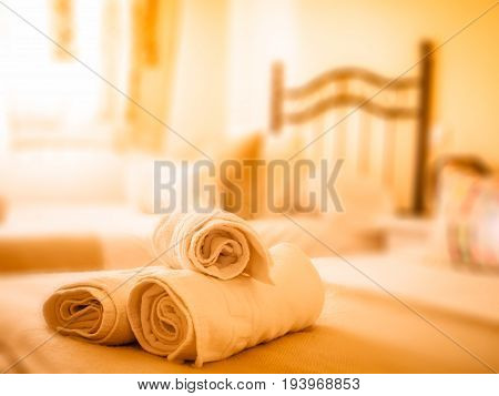Clean towels on a bed in sun illuminated bedroom of a holiday apartment