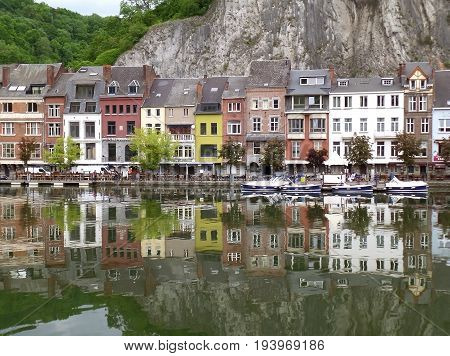 Reflections of colorful buildings along the Meuse river at Dinant, Wallonia Region, Belgium