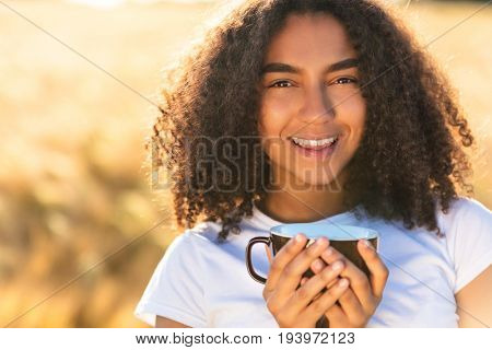 Beautiful happy mixed race African American girl teenager female young woman smiling with perfect teeth white,drinking coffee or tea outdoors