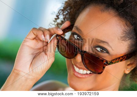 Beautiful young mixed race black African American woman smiling with perfect teeth and wearing sunglasses