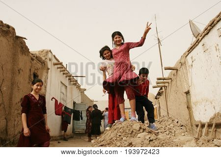 Khiva Uzbekistan - March 08 2009: Children stand on the mountain from the remains of a house that was destroyed by time.
