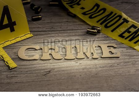 The word CRIME is assembled with wooden letters