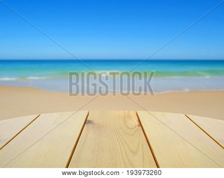 Wooden table for product display on blurred beach background