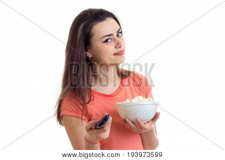 Portrait of a pretty girl with remote control in hand, and pop-corn is isolated on a white background