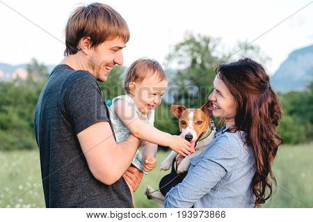 Close-up portrait of happy family with pet - jack russel terrier walking outside. Baby and dog.