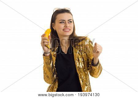 beautiful girl in frenzy gold jacket laughs and keeps bananas in the hands isolated on white background