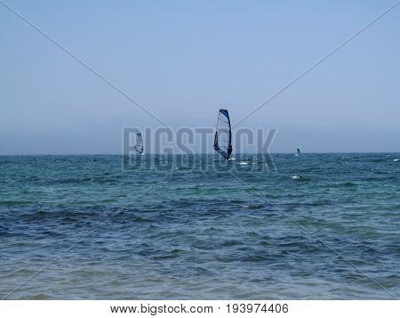 Two windsurfers are located symmetrically on the sea surface. Blue-turquoise sea clear blue sky without clouds and two surfers are doing sports