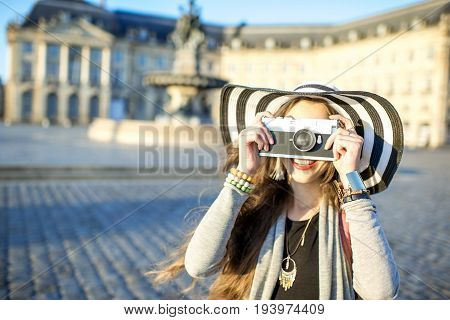 Young woman tourist with photo camera on the famous Bourse square with beautiful buildings and fountain in Bordeaux city during the morning