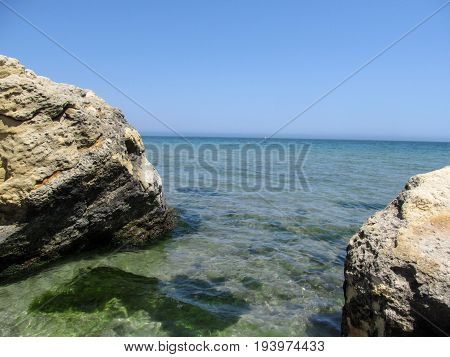 Two Beige-brown rocks are symmetrical around the edges of the photo and between them the blue-turquoise sea. A clear sunny day and a clear sky without clouds