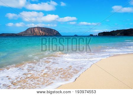 a view of the white sand of Playa de la Conchas beach in La Graciosa island, in the Canary Islands, Spain, with the Montana Clara Island to the left