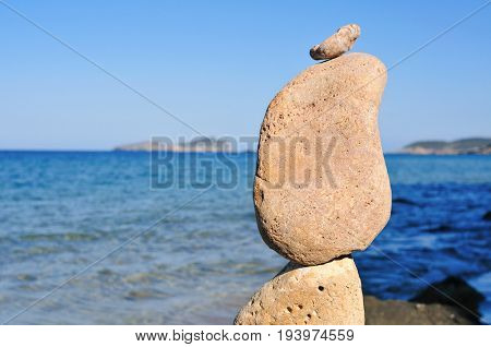 closeup of a stack of balanced stones in Ibiza Island, in Spain, with the Mediterranean sea in the background