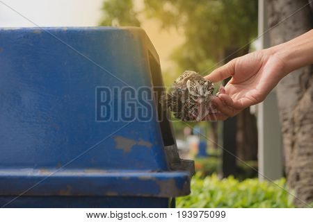 Female hand throwing crumpled paper into blue plastic trashcan.