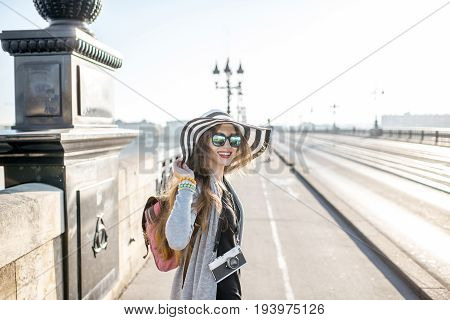 Young woman tourist walking on the famous Pierre bridge in Boredaux city in France