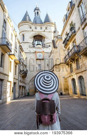 Young woman tourist with big hat standing back in front of the famous bell tower in Bordeaux city in France
