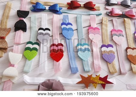 Set of colorful elastic decorated headbands. Bright handmade hair accessories with felt hearts decoration. Beauty, fashion, style concept