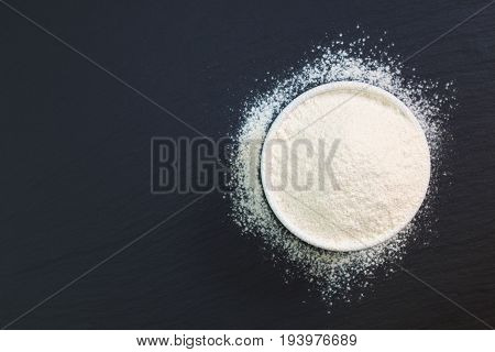 Wheat flour in white cup on black slate stone plate with copy space for preparing baking or pasta