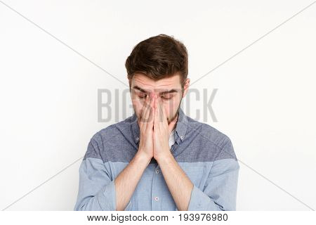 Young stressed man cover his face with hands. Exhausted stressed guy portrait, isolated on white background