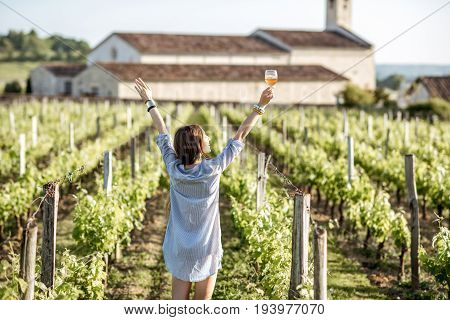 Young woman with glass of wine enjoying beautiful sunset view on the vineyard in Bordeaux region in France