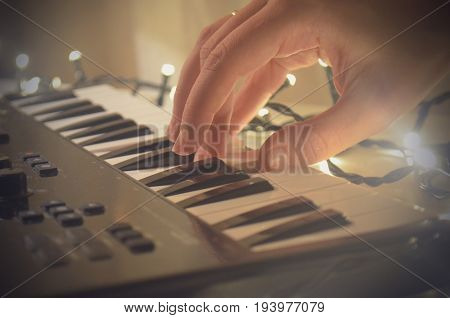 Woman hand playing Piano or electone midi keyboard, electronic musical synthesizer white and black key. Lighting, garland. Vintage effect, instagram filter style.