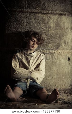 Sad Child Sleeping While Tied In Straight Jacket