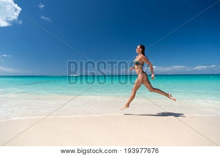 Woman in sexy swimsuit running on sea beach with white sand turquoise water and blue sky on sunny day on natural environment. Sun tanning bathing. Summer vacation. Rest relaxing active leisure
