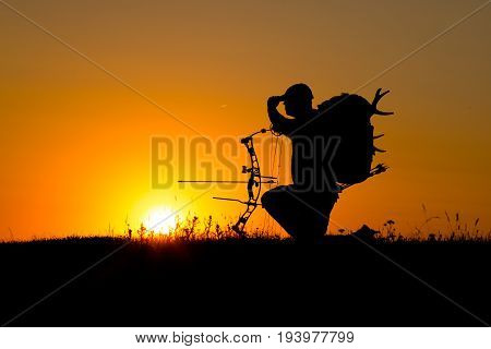 Silhouette of a bow hunter on the sunset
