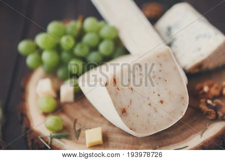 Cheese platter, gouda herb and blue roquefort cheese on wooden board with grapes and nuts, still life