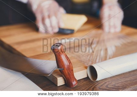 Grocery shop background. Shop assistant wrapping a piece of cheese. Packing order at grocery shop in cling film on wooden table, background