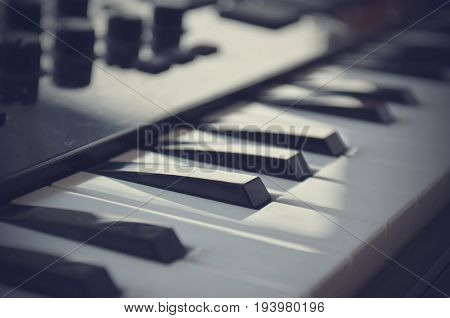 Piano or electone midi keyboard, electronic musical synthesizer white and black key. Vintage effect, instagram filter style. Close up.