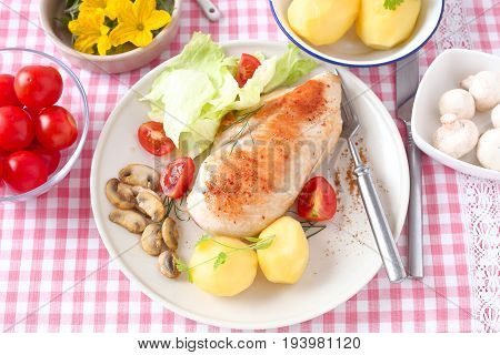 Boiled chicken fillet with potato and lettuce.