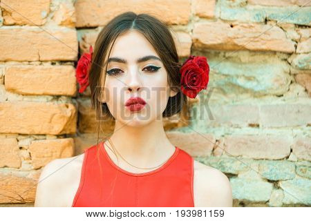 woman or cute girl young fashion model with red lips makeup and fresh roses flowers in brunette hair fashionable hairstyle posing outdoors on old brick wall. Beauty and hairdressing salon