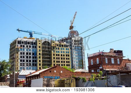 SAMARA, RUSSIA - JUNE 21, 2017: A house under construction and construction cranes on background of blue sky. Construction is conducted on Krasnoarmeyskaya Street.