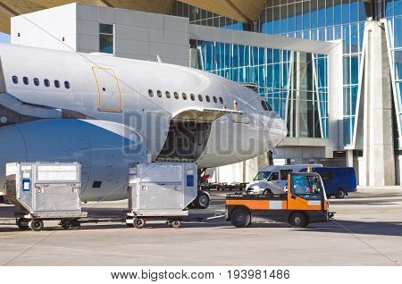 Aircraft Standing In The Parking Lot At The Airport, Ready To Load Passengers Luggage