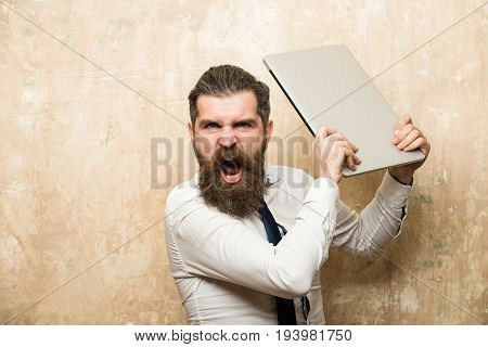 businessman. bearded man with long beard and stylish hair on shouting face in tie and white shirt hold laptop on textured beige background digital marketing and business agile business