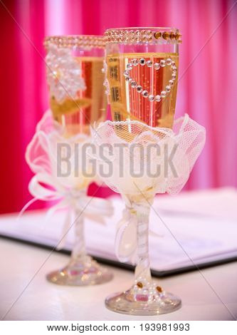 Beautifully decorated wedding glasses on the table.
