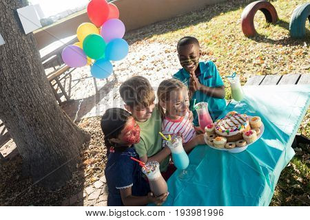 High angle view of happy children with face paint having food and drinks at park