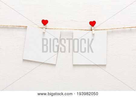 White blank cards on rope, love notice backdrop. Creative romantic reminder, small sheets of paper on clothespin with red hearts, bright memo background