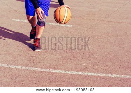 Young man on basketball court dribbling with ball. Streetball, training, activity. Real and authentic,