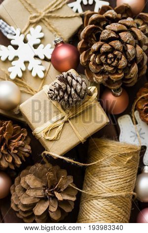 Process of praparing and wrapping Christmas and New Year gits natural materials craft paper twine pine cones wood ornaments snow flake baubles top view