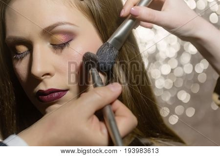 fashion model with closed eyes and stylish eyeshadows lips on glowing background. Hands of visagistes putting powder on face skin with two makeup brushes. Visage cosmetics fashion victim