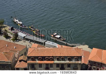GAIA, PORTUGAL - AUGUST 7, 2015: Roofs and traditional wooden boats used to transport Wine on the Douro river in Gaia Portugal.