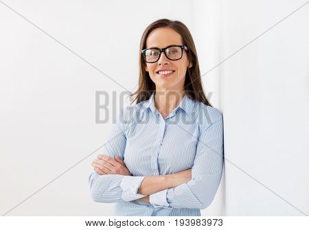 people, business and vision concept - happy smiling middle aged woman in glasses at office
