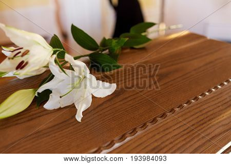 funeral and mourning concept - white lily flower on wooden coffin lid at funeral in church