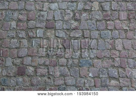 Granite cobblestoned pavement background. Stone pavement texture. Abstract background of old cobblestone pavement close-up in Prague.