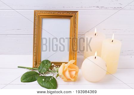 Empty frame candles and roses flowers on white wooden background. Place for text. Selective focus is on frame.